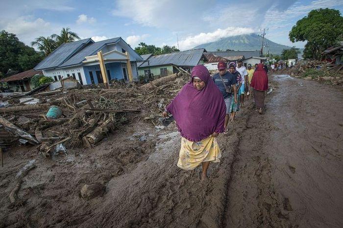 Warga selamat mengungsikan diri dari rumahnya setelah banjir bandang dan tanah longsor menerjang NTT pada Minggu (4/4/2021)